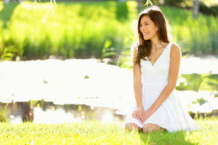 sit down: Asian woman sitting in park in spring or summer. Beautiful young woman smiling happy wearing white sundress sitting down in grass in park, Cute mixed race Asian Caucasian woman in her 20s. Stock Photo