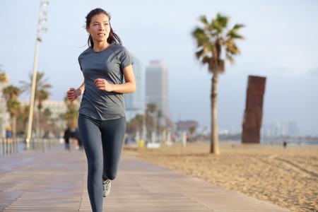 alone: Mujer corriente que activa en la playa de Barcelona, ??Barceloneta. Estilo de vida saludable, formación corredor exterior de la muchacha en el paseo marítimo. Mezcla de raza asiática fitness mujer caucásica trabajando al aire libre en Cataluña, España.