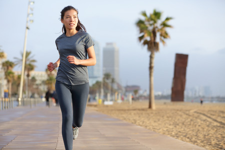 Running woman jogging on Barcelona Beach, Barceloneta. Healthy lifestyle girl runner training outside on boardwalk. Mixed race Asian Caucasian fitness woman working out outdoors in Catalonia, Spain.