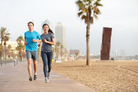 gezonde mensen: Hardlopen paar joggen op het strand van Barcelona, Barceloneta. Gezonde levensstijl mensen lopers training buiten op promenade. Multiraciale paar, Aziatische vrouw, blanke fitness man uit te werken, Spanje. Stockfoto