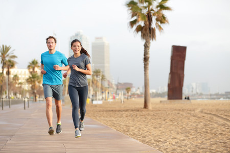 people and nature: Running couple jogging on Barcelona Beach, Barceloneta. Healthy lifestyle people runners training outside on boardwalk. Multiracial couple, Asian woman, Caucasian fitness man working out, Spain.