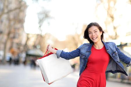 asian girl shopping: Shopping girl happy shopping outside. Beautiful woman running joyful with shopping bags outdoors wearing denim jacket on La Rambla, Catalonia, Barcelona, Spain. Mixed race Asian Caucasian female model Stock Photo