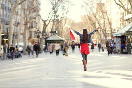 バルセロナ、ランブラス通りのショッピング女性。女性の買い物客のショッピング バッグを調達したと離れて幸せ歩いて。有名なランドマークでス