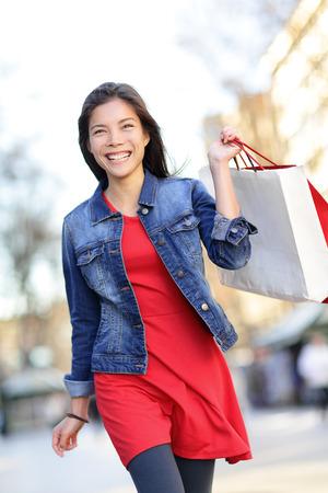 Shopper - vrouw winkelen buiten met boodschappentassen lopen buiten lachend dragen denim jasje. Mooi gemengd ras Aziatische Kaukasische meisje in haar jaren '20. Stockfoto