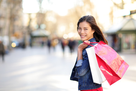 Žena nakupování - shopper dívka venku s úsměvem šťastný hospodářství nákupní tašky. Portrét ženy nakupující pohledu na kameru na pěší ulici La Rambla, Barcelona, Španělsko. Smíšený závod asijské ženy.