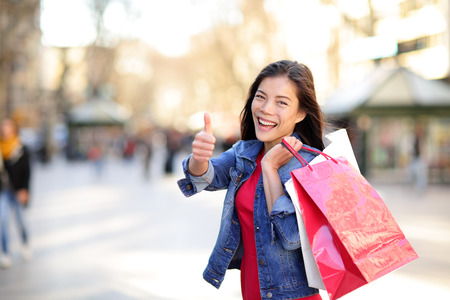 Shopping woman thumbs up on La Rambla, Barcelona, Spain. Happy Shopper girl holding shopping bags up excited outside on walking street. Mixed race Asian Caucasian female model. Stock Photo