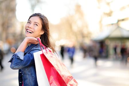 Mujer feliz de compras y mirando a otro lado en el espacio de la copia en el exterior. Chica Shopper celebración bolsas de la compra hasta emocionada al aire libre en la calle caminando. Raza mixta modelo asiático mujeres de raza caucásica en la Rambla, de Barcelona.