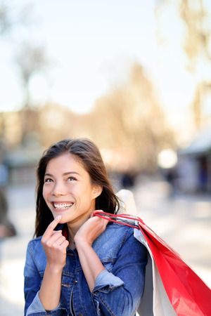 Shopping woman thinking looking up outdoors. Shopper girl holding shopping bags up excited outside on walking street. Mixed race Asian Caucasian female model cheerful on La Rambla street Barcelona. Stock Photo