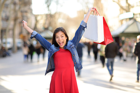 arms raised: Shopping woman happy on La Rambla street Barcelona. Shopper girl holding shopping bags up excited outdoors on walking street. Mixed race Asian Caucasian female model cheerful in Spain.
