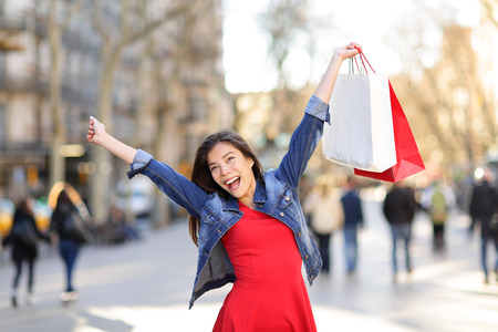 Happy shopping woman on La Rambla street Barcelona. Shopper girl holding shopping bags up excited outdoors on walking street. Mixed race Asian Caucasian female model in denim jacket. Spain. photo