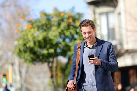 스마트 폰을 사용하는 젊은 도시 전문적인 사람. 그라시아, 바르셀로나, 카탈로니아, 스페인에 재킷을 입고 앱 문자 메시지 SMS 메시지를 사용하여 모바