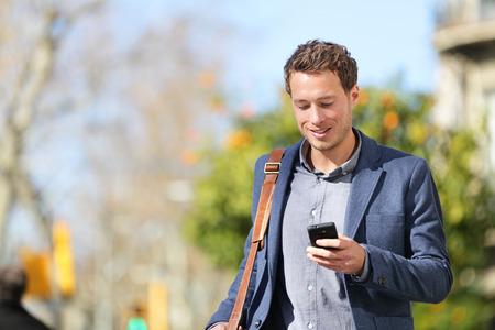 비즈니스맨: 그라시아, 바르셀로나, 카탈로니아, 스페인에 재킷을 입고 스마트 폰에 앱 문자 메시지 SMS 메시지를 사용하여 거리에있는 스마트 폰 걷고 전문 젊은 도시 사업가.