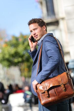chaqueta de cuero: Hombre de negocios en el tel�fono inteligente para caminar en la calle hablando por tel�fono m�vil inteligente sonriente llevaba chaqueta y bolso del ordenador port�til de cuero en el Passeig de Gracia, Barcelona, ??Catalu�a, Espa�a. Foto de archivo
