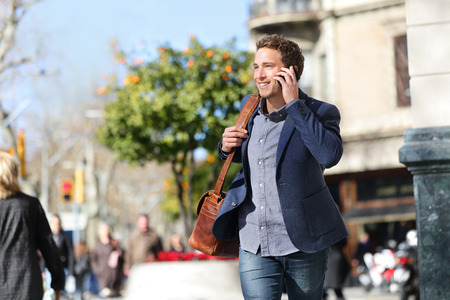 casual fashion: Young urban businessman on smart phone running in street talking on smartphone smiling wearing jacket and leather laptop bag on Passeig de Gracia, Barcelona, Catalonia, Spain. Stock Photo