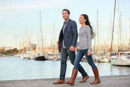 parejas caminando: Joven pareja caminando al aire libre en el puerto viejo, Port Vell en Barcelona Cataluña, España. Mujer feliz romántico y el hombre de la mano disfrutando de la vida y el romance fuera.