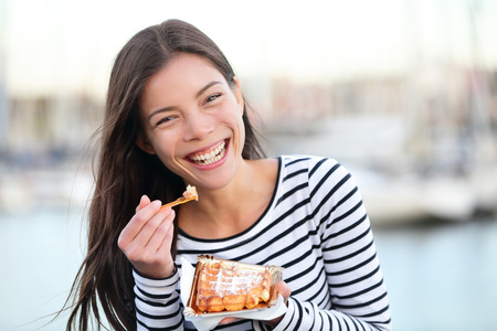 Waffles - woman eating waffle happy outdoors smiling laughing looking at camera. Beautiful girl eating food snack outside.