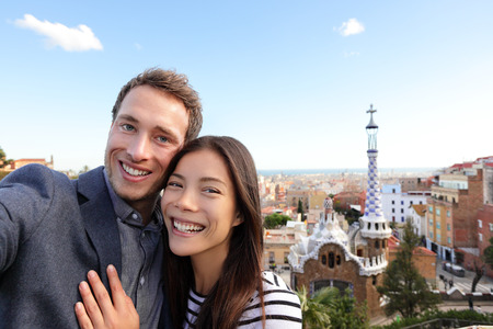 Happy travel couple in Park Guell, Barcelona, Spain. Beautiful young multiracial couple looking at camera taking selfie smiling happy having fun on Europe vacation trip.  Stock Photo