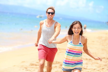 lovers holding hands: Beach couple enjoying fun romantic vacation holiday. Happy young trendy cool multi-ethnic couple running having fun laughing together smiling happy. mixed race Asian woman, Caucasian man.