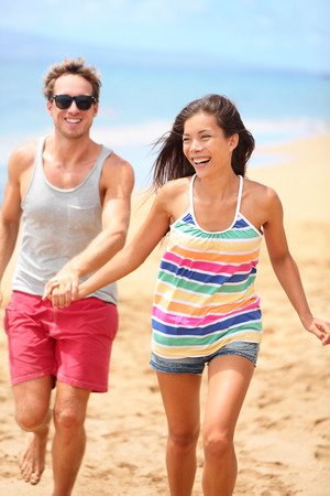 Beach vacation - happy fun romantic couple running holding hands. Two cool trendy hipster people playful on summer travel holidays. Interracial young couple, Asian woman, Caucasian man at ocean sea. photo