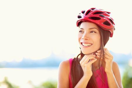 ciclismo: Casco de la bici - la mujer que pone el casco ciclismo en el exterior durante el paseo en bicicleta. Foto de archivo