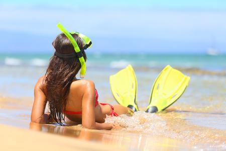 스노클링 마스크와 지느러미로 모래에 누워 여름 해변 휴가 여행에 편안한 여자가 미국, 하와이, 마우이에 화창한 여름 날에 태양을 즐기는 행복 미소.