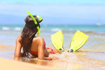 Woman relaxing on summer beach vacation holidays lying in sand with snorkeling mask and fins smiling happy enjoying the sun on sunny summer day on Maui, Hawaii, USA. photo