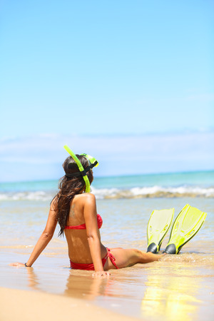 Woman relaxing on summer beach vacation holidays lying in sand with snorkeling mask and fins smiling happy enjoying the sun on sunny summer day. Multi-ethnic Asian Chinese  Caucasian woman model. photo