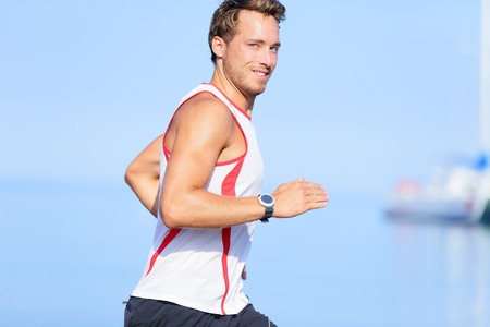 Running man runner looking at camera smiling funny flirtatious or playful. Handsome good looking male fitness model jogging outside on beach training living healthy lifestyle. Young guy in his 20s. photo