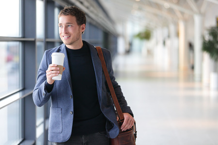 Businessman drinking coffee walking in airport. Casual urban professional smiling happy wearing suit jacket holding disposable coffee cup on travel. Handsome male model in his twenties. photo