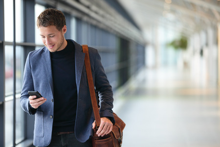 traveller: Man on smart phone - young business man in airport. Casual urban professional businessman using smartphone smiling happy inside office building or airport. Handsome man wearing suit jacket indoors.