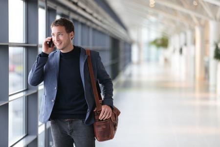 Stedelijke zakenman praten op slimme telefoon reizen lopen binnen in de luchthaven. Casual jonge zakenman dragen pak jas en schoudertas. Knap mannelijk model in zijn 20s. Stockfoto