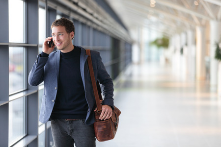 Urban business man talking on smart phone traveling walking inside in airport. Casual young businessman wearing suit jacket and shoulder bag. Handsome male model in his 20s. Stock Photo