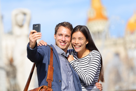 traveller: Lovers - young couple happy taking selfie photo with smart phone camera. Modern urban city man and woman having fun taking self portrait picture with smartphone, Catalonia Square, Barcelona, Spain