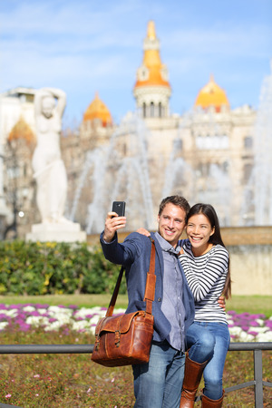 Tourist travel couple taking selfie in Barcelona with smart phone camera. Trendy cool urban city couple, Cauasian man, Asian woman traveling together, Placa de Catalunya, Catalonia Square, Barcelona, Spain photo