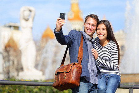 traveller: Happy urban city couple on travel in Barcelona taking selfie self portrait photograph with smart phone camera. Happy young man and woman on Placa de Catalunya, Catalonia Square, Barcelona, Spain.
