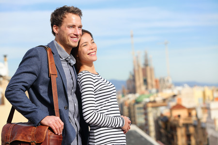 Happy romantic couple looking at view of Barcelona. Smiling lovers enjoying cityscape with famous landmarks. Stylish urban young man and woman on travel in Catalonia, Spain, Europe.