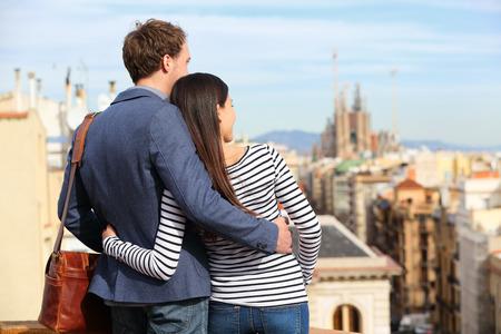 persona viajando: Pareja romántica mirando vista de Barcelona. Amantes felices disfrutando de paisaje urbano con lugares de interés turístico. Joven urbana con estilo y mujer en los viajes en Cataluña, España, Europa. Foto de archivo