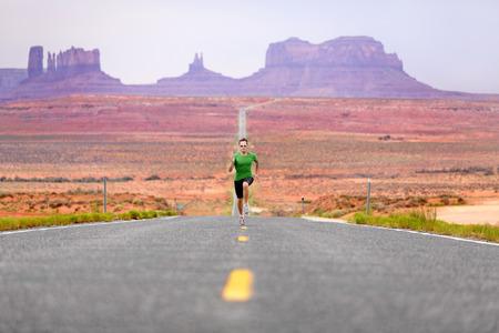 記念碑の谷で道路にスプリント ランナー男 - 実行しています。成功のための学習の高速スプリントのコンセプト。素晴らしい風景の自然の中でワー
