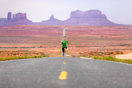 Running man - runner sprinting on road by Monument Valley. Concept with sprinting fast training for success. Fit sports fitness model working out in amazing landscape nature. Arizona, Utah, USA. photo