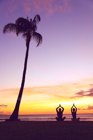 ヨガ瞑想 - 夕暮れ時の人々 のシルエット。カラフルな空に対する自分の手で蓮華座でビーチに座って夕日でヨガ カップルのシルエットです。男と女 写真素材 - 26954319