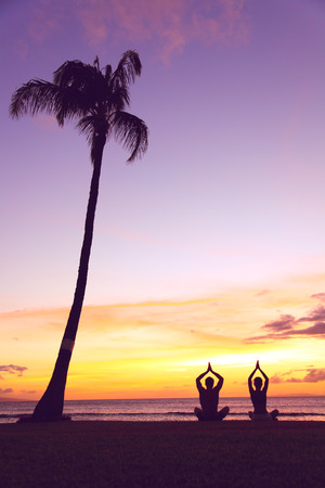 Yoga meditation - silhouettes of people at sunset. Silhouette of a couple practising yoga at sunset sitting on a beach in the lotus position with their hands raised against colorful sky. Man and woman Imagens