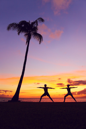 Yoga meditation people meditating training warrior pose outside by beach at sunrise or sunset. Woman and man yoga exercising training in serene ocean landscape. Silhouette of couple against sunset photo