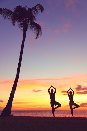 Serene yoga people training in sunset in tree pose meditating outdoors by beach ocean sea. Couple, man and woman working out training in serene ocean landscape. Silhouette against sunset photo