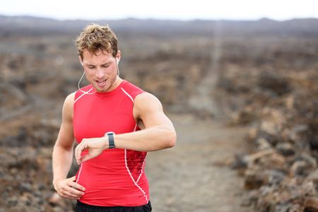 Lopende atleet man op zoek naar hartslagmeter GPS horloge Stockfoto