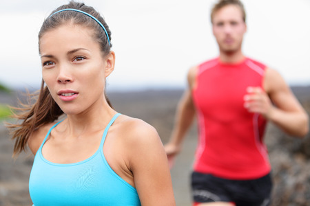 Close up of girl jogging outside with man in background photo
