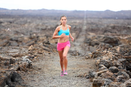 Runner woman triathlete trail running cross country running outdoors on volcano photo