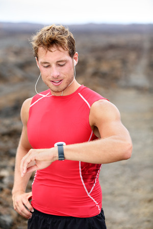Running man looking at heart rate monitor GPS watch photo