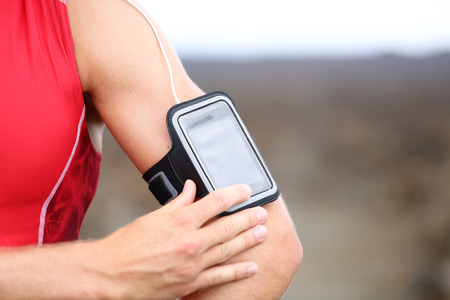 male runner listening to music adjusting settings on armband for smartphone photo