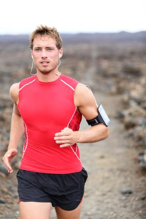 Man triathlete jogging listening to music on smart phone photo