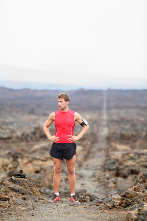 Fit handsome athlete taking break standing in amazing volcano landscape on Big Island, Hawaii, USA. photo